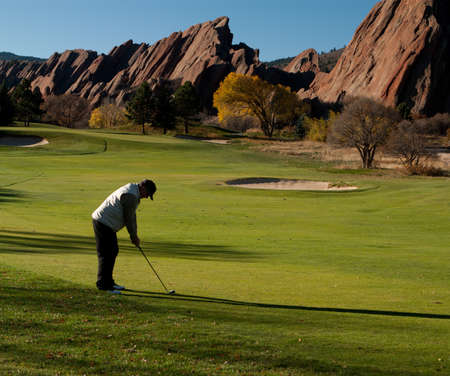 Man Golfing on a Golf Course in Autumn With Large Red Rocks Stock Photo