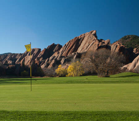 Hole and Flag on Mountain Golf Course With Large Red Rocks Stock Photo