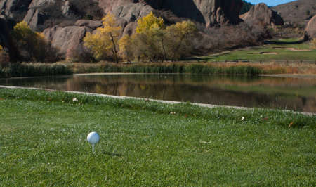 Golf Ball on the Green Next to a Lake With Large Red Rocks