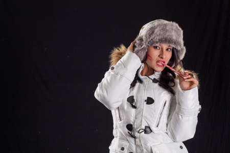 Latina Snow Bunny in White Puffy Coat and Boots With Candy Cane In Mouth Stock Photo