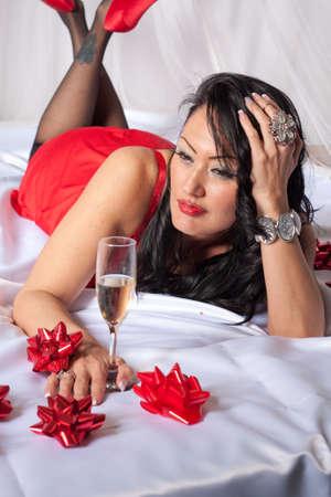 Mujer de Latina que pone en cama con sábanas de raso blanco con sexy vestido rojo y zapatos de tacón alto rojos Foto de archivo - 17017592