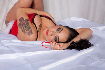 Woman With Brown Hair, Green Eyes, and Tattoos in Sexy Red Lingerie on a Bed With White Satin Sheets photo