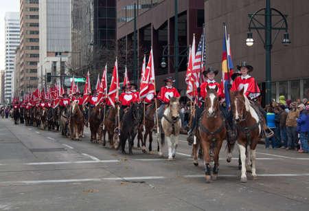 colorado flag: Denver, Colorado January 10, 2013 National Western Stock Show Parade  Westernaires Riding Horseback Down the Streets of Denver With American Flag and Colorado Flag