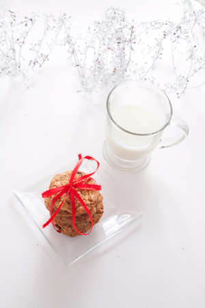 Chocolate Chip Cookies Tied With a Red Bow on a Clear Plate With a Glass of Milk With Garland Stock Photo - 17337969
