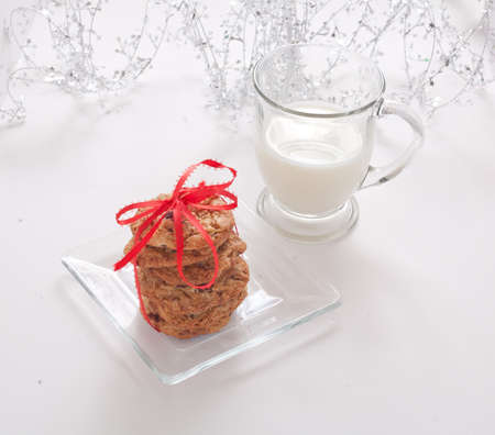 Chocolate Chip Cookies Tied With a Red Bow on a Clear Plate With a Glass of Milk With Garland photo