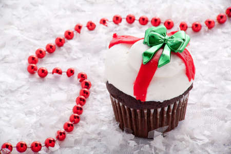 Chocolate Christmas Cupcake With White and Red Frosting and a Green Bow Surrounded by Red Beads and Snow