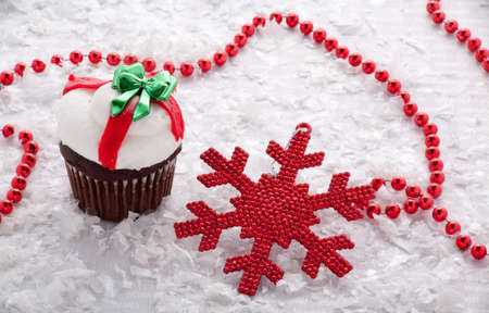 Chocolate Christmas Cupcake With White and Red Frosting and a Green Bow Surrounded by Red Beads, Snow and Red Snowflake