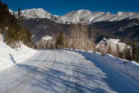 bridget calip: Snow Covered Road on a Sunny Winter Morning on Many Parks Curve in Rocky Mountain National Park