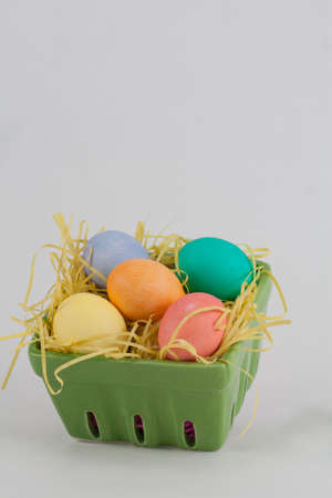 Multicolored Easter Eggs in Green Crate With Yellow Grass