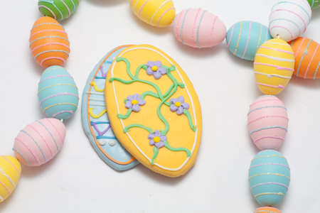 Easter Cookies in the Shape of an Egg Decorated with Blue and Yellow Frosting With Egg Glitter Garland Stock Photo - 18533600