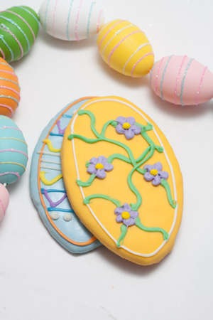Easter Cookies in the Shape of an Egg Decorated with Blue and Yellow Frosting With Egg Glitter Garland Stock Photo - 18533590