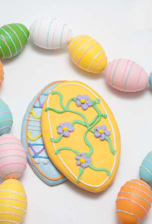 Easter Cookies in the Shape of an Egg Decorated with Blue and Yellow Frosting With Egg Glitter Garland Stock Photo