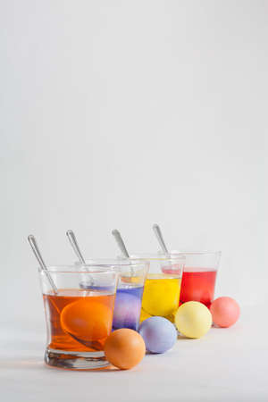 Clear Glasses Filled With Red, Orange, Blue and Yellow Easter Egg Dye and Eggs With Silver Spoon Stock Photo - 18533589