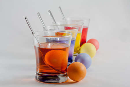 Clear Glasses Filled With Red, Orange, Blue and Yellow Easter Egg Dye and Eggs With Silver Spoon Stock Photo - 18533647