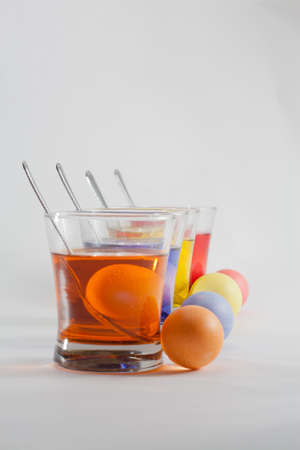 bridget calip: Clear Glasses Filled With Red, Orange, Blue and Yellow Easter Egg Dye and Eggs With Silver Spoon