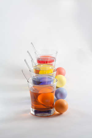 Clear Glasses Filled With Red, Orange, Blue and Yellow Easter Egg Dye and Eggs With Silver Spoon