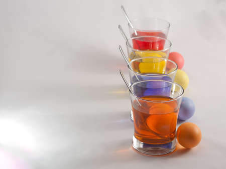 Clear Glasses Filled With Red, Orange, Blue and Yellow Easter Egg Dye and Eggs With Silver Spoon Stock Photo - 18533601