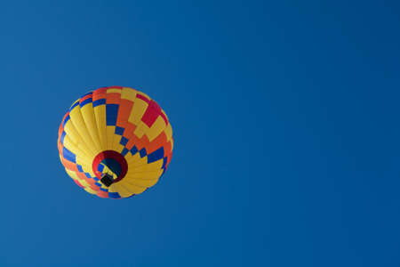 Blue, Orange, Yellow and Red Hot Air Balloon with Clear Blue Skies Stock Photo - 18986423
