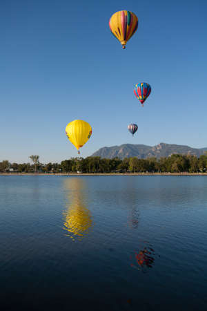 Colorful Hot Air Balloons Flying Over a Lake with Rocky Mountains and Clear Blue Skies Stock Photo - 18986427