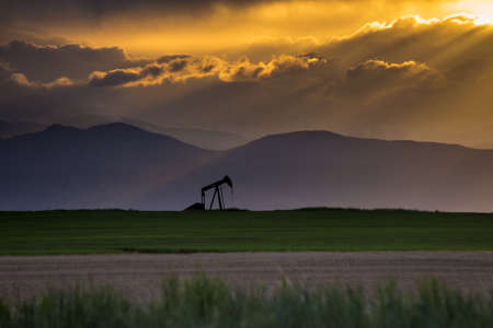 Rocky Mountains Pump Jack With Crepuscular Rays and Dramatic Orange Clouds