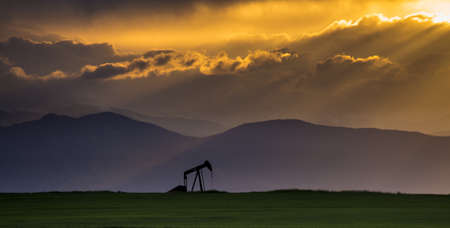 bridget calip: Oil Pump in Green Field with Mountains and Crepuscular Rays with Dramatic Clouds