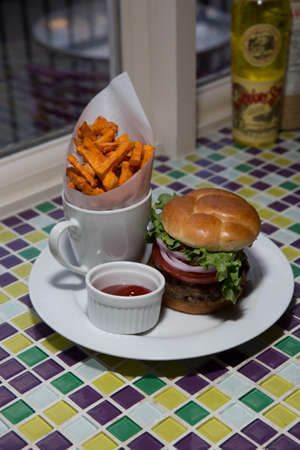 all american burger: Juicy All American Cheeseburger With Red Onion, Lettuce, Hand Cut Sweet Potato Fries and Ketchup