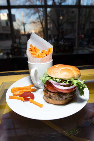 Gourmet Hamburger With Fresh Tomatoes, Red Onions, Lettuce and Sweet Potato Fries With Ketchup