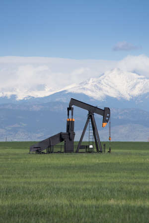 jacks: Pump Jacks in Green Field With Snow Covered Rocky Mountains and Blue Sky Stock Photo