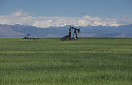 bridget calip: Oil Pumps in Green Field With Snow Covered Rocky Mountains and Blue Sky Stock Photo