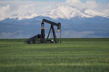 Pump Jacks in Green Field With Snow Covered Rocky Mountains and Blue Sky Stock Photo