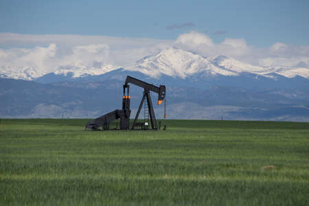 Oil Pumps in Green Field With Snow Covered Rocky Mountains and Blue Sky Stock Photo