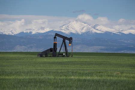 rocky mountains: Olie pompen in Groen Gebied Met Sneeuw Behandelde Rocky Mountains en Blue Sky Stockfoto
