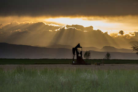crepuscular: Rocky Mountains Pump Jack With Crepuscular Rays and Dramatic Orange Clouds