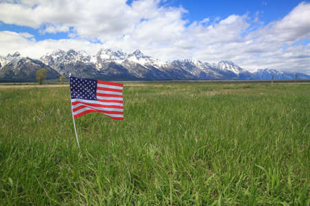 American Flag in Green Meadow Flanking the Rocky Mountains photo