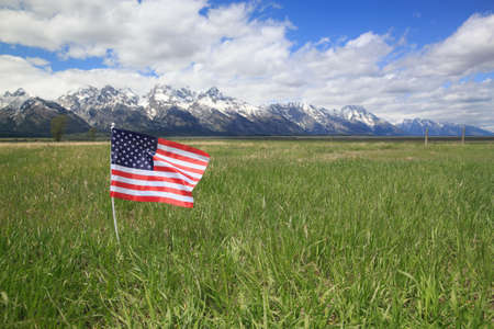 American Flag in Green Meadow Flanking the Rocky Mountains
