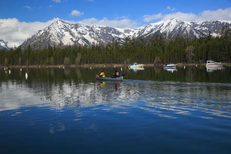 Couple Canoeing in a Lake in the Rocky Mountains Covered in Snow