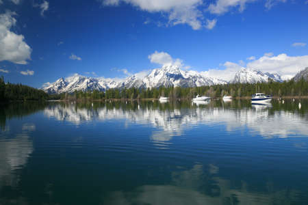 Speed Boats in a Marina in a High Rocky Mountain Lake With Snow Covered Mountains photo