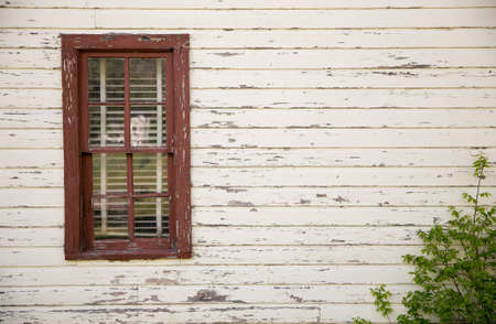 Eight Pane Red Window With White Weathered Wood and Green Shrub Stock Photo