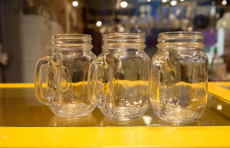 Clear Glass Mugs on Yellow Bar Stock Photo