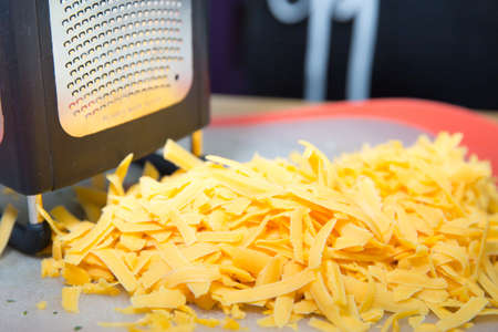 Pile of Yellow Grated Cheddar Cheese With Stainless Steel and Black Grater