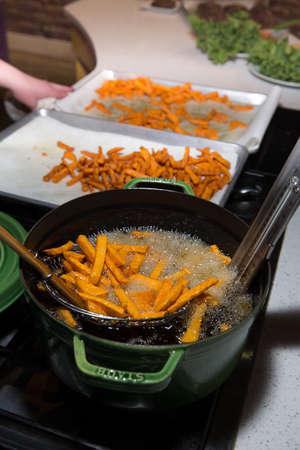 Fresh Sweet Potato Fries Frying in Oil in Metal Basket Stock Photo