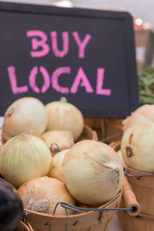 bridget calip: Organic White Onions in Baskets with Buy Local Chalkboard Sign at the Farmers Market
