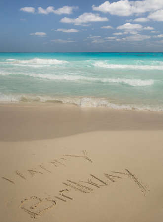 Happy Birthday written in the sand by the turquoise Caribbean Sea with cumulus clouds