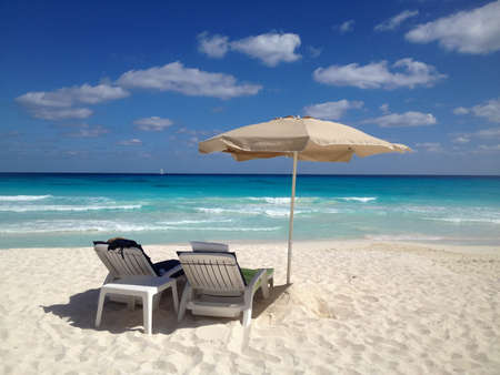 Two Beach Chairs on a White Sand Beach With Umbrella and Turquoise Water With Sailboat in the Distance Stock Photo