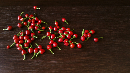 chiles picantes: Red hot peppers on dark wood