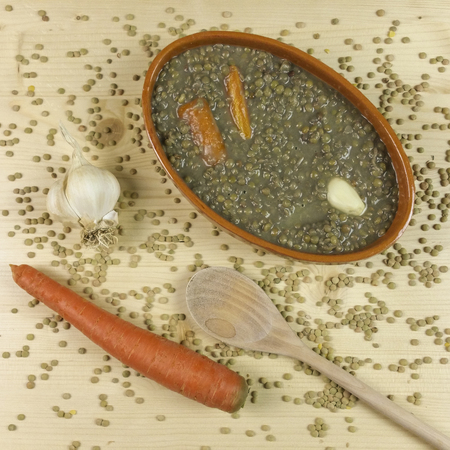 lentils with carrots and garlic on wood background - top view