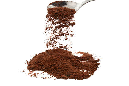 trickling: cocoa powder trickling from silver spoon Stock Photo
