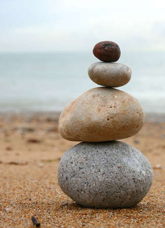 stacked up: 4 stones stacked up on beach Stock Photo