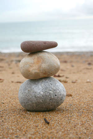 stacked up: three stones stacked up on beach Stock Photo