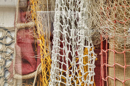 fishermans net: Fishing nets on display in a shop window, yellow and white nets hanging with red and brown canvas as backdrop. Stock Photo